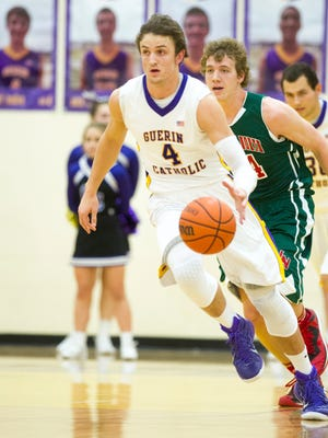 Guerin Catholic High School senior Matt Holba (4) races the ball up court during first half action. Guerin Catholic High School hosted Lawrence North High School in boys varsity basketball, Friday, Dec. 19, 2014.