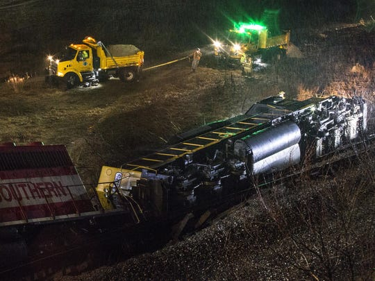 Firefighters and workers investigate a derailed train near U.S. 131 under 28th Street in Grand Rapids, on Tuesday.
