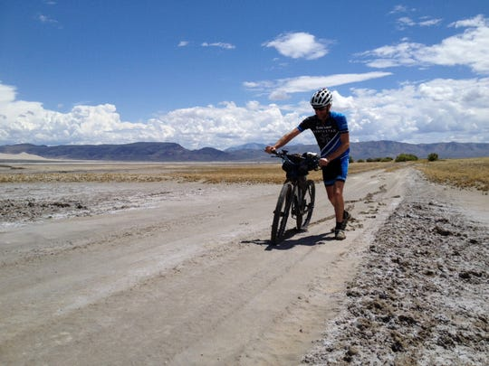 Blake Bockius of Truckee pushes his bike through mud near Fallon on the route of the Comstock EPIC, a 552-mile race across Nevada.