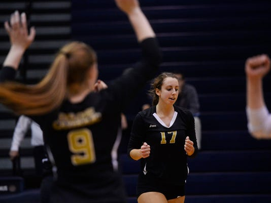 Delone Catholic's Sarah Senft, center, cheers with teammates after a point in the third game during the YAIAA girls' volleyball tournament championship at Dallastown Area High School on Oct. 27.  (Kate Penn -- GameTimePA.com)
