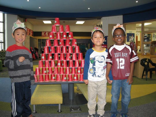 Henry Wang, Rentaro Takeshita, and Luke Mandl build with 100 cups.