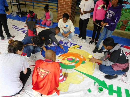 Students working on the peace mural