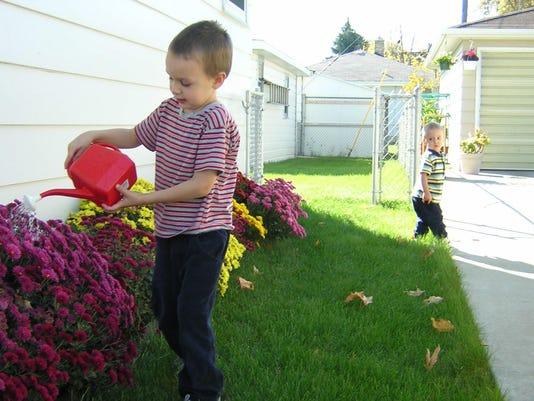 two-kids-watering-plants-1502371