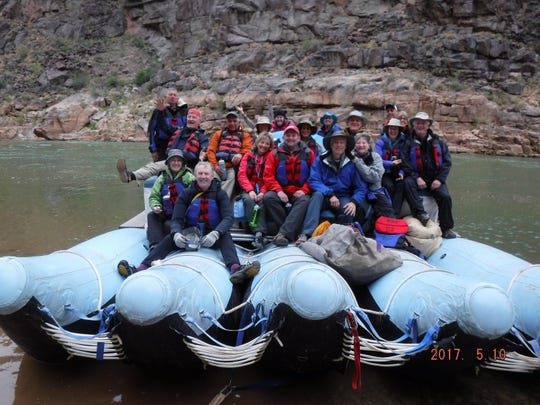 A group of 18 travelers and their guides on the Colorado River in the Grand Canyon.