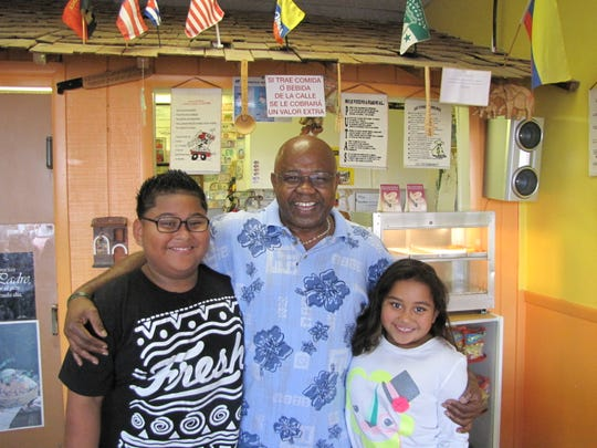William Mosquera, who runs Las Delicias Restaurant in North Fort Myers, spends time with his grandchildren, Matthew Salguero, left, and Shalom Salguero at the eatery.