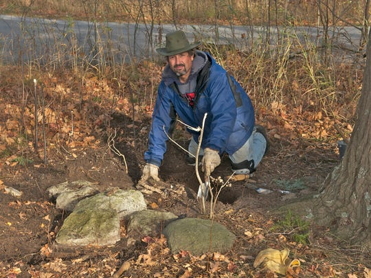 Tom Skubal works at excavating the grist millstone at Shea's Lake in November.