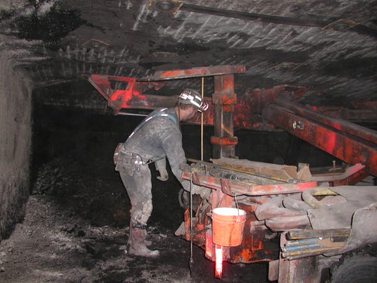 A coal miner puts bolts up to support a mine roof.