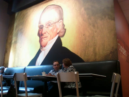 Couple enjoying a quiet cup of java at the new Founders Café under the watchful eye of Nathaniel Rochester. This was just moments before 100 people arrived to celebrate its grand opening.