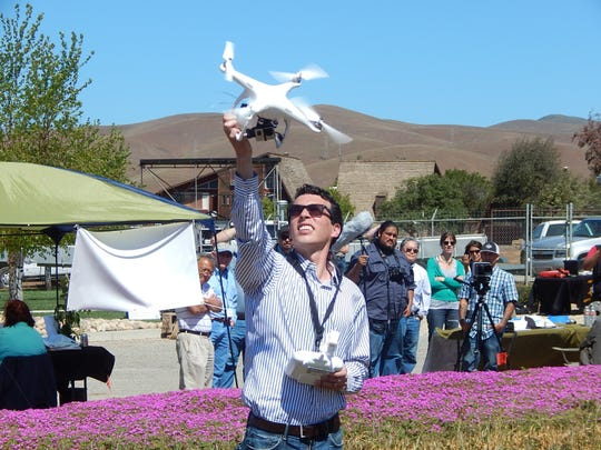 Cliff Hogan, co-founder of EagleEye Ag Tech in Salinas, hovers the drone down into his hand during a demonstration Thursday at Converted Organics in Gonzales.