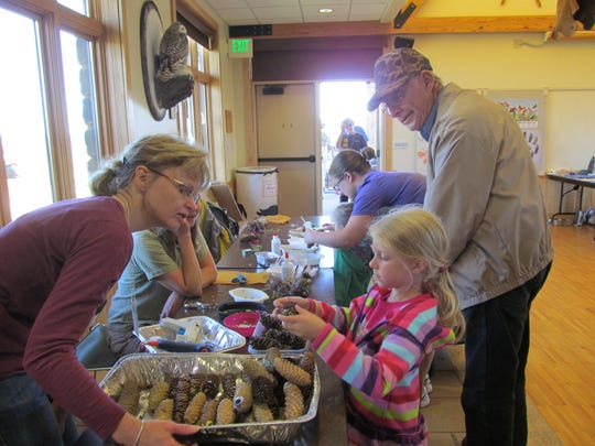 Steve Bogaczyk and his granddaughter create an animal creature with help of volunteers during a Grandparents Day event Sunday at Mead Wildlife Area in Milladore.