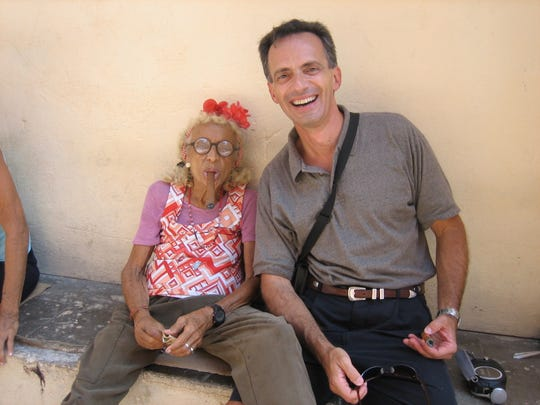 Dr. Fernando Riveron posed for this photograph with an old woman smoking a cigar during his 2007 visit to Cuba.