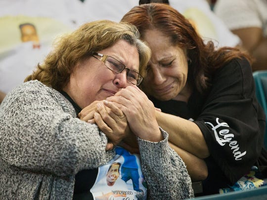 Patricia Sepulveda, left, and Dora Olvera weep during a community prayer service Thursday at the Dunbar Community School in Fort Myers. Both mothers had sons that were murdered in 2016. More than 150 people attended the vigil held in remembrance of Fort Myers homicide victims.
