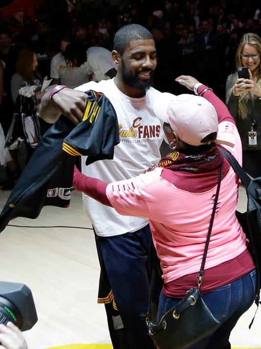 Cleveland Cavaliers' Kyrie Irving hugs a fan before giving her his jersey for Fan Appreciation night after an NBA basketball game between the Toronto Raptors and the Cleveland Cavaliers, Wednesday, April 12, 2017, in Cleveland. (AP Photo/Tony Dejak)