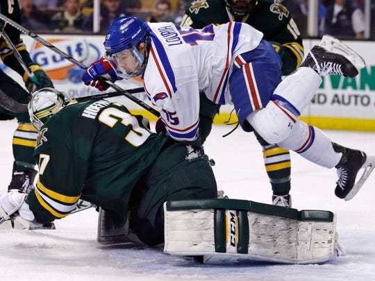 UMass Lowell forward Michael Louria, top, slams into Vermont goalie Brody Hoffman, who drops to make the save on the puck, during the second period of the Hockey East semifinals in Boston on Friday. Louria was charged with goalie interference on the play.