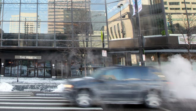 A car zips past Downtown's Westin Hotel, which is undergoing renovation.