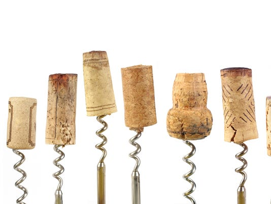 Different size wine corks with the corkscrew in each of them