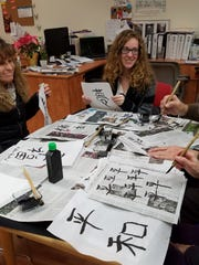 Participants take part in a past kakizome event, the Japanese ritualized first calligraphy writing of the year. This year's event will be held Jan. 6.