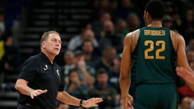 Michigan State coach Tom Izzo talks with Miles Bridges (22) during the first half of an NCAA college basketball game against Connecticutduring the Phil Knight Invitational tournament on Friday, Nov. 24, 2017, in Portland, Ore.