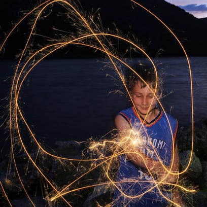 Milo Shuk, 9 of Philipstown, twirls gold colored sparklers