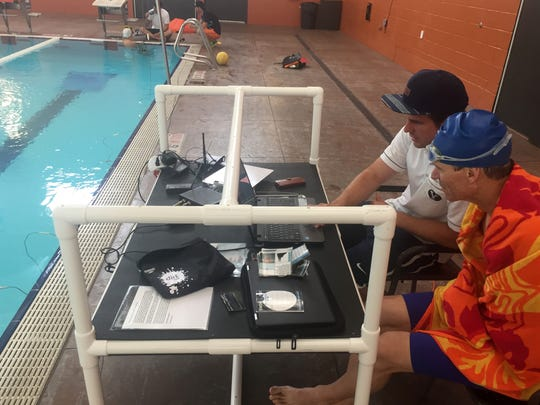 Truer Caywood, right, gets some tips on his swimming technique while he and swim coach Garret Beaman look at a computerized graph of the power in his strokes as they sit beside the pool at the Washington City Community Center during the Balanced Art Multisport triathlon camp Friday, April 14, 2016.