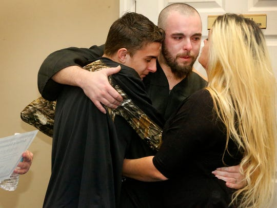 Rutherford County jail inmate Patrick Hix, center, hugs his girlfriend's son Levi Charron, left and his girlfriend Tonya Charron, right at the end of a small party after passing the HiSET exam, earning him a high school equivalency diploma during a graduation ceremony on Nov. 30, 2017, at the Rutherford County Adult Detention Center.