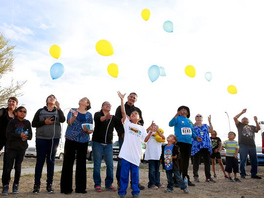 Families and friends honor Alex Kee Yazzie and other police officers who died in the line of duty during the Healing Begins-Never Lose Hope honor walk on Wednesday at the Navajo police station in Shiprock.