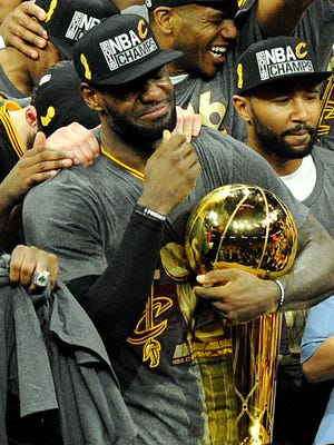 Cleveland Cavaliers forward LeBron James (23) celebrates with Larry O'Brien Championship Trophy after beating the Golden State Warriors in game seven of the NBA Finals at Oracle Arena. James was named AP Athlete of the Year.