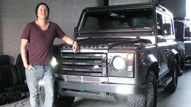 Matt Perlman poses with one of the Land Rover Defenders that he is updating through his import and restoration business, West Coast Defenders in Los Angeles