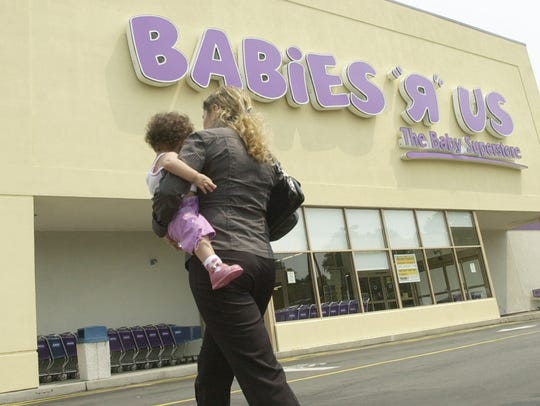 """A woman carrying a child walks towards the Babies """"R"""""""
