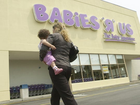 "A woman carrying a child walks towards the Babies ""R"" Us store in North Brunswick, N.J., Wednesday, Aug. 11, 2004. Toys ""R"" Us Inc., faced with fierce competition from discounters, particularly Wal-Mart Stores Inc., said Wednesday it is exploring the possible sale of its global toy business as it pursues separating its toy and baby product divisions."