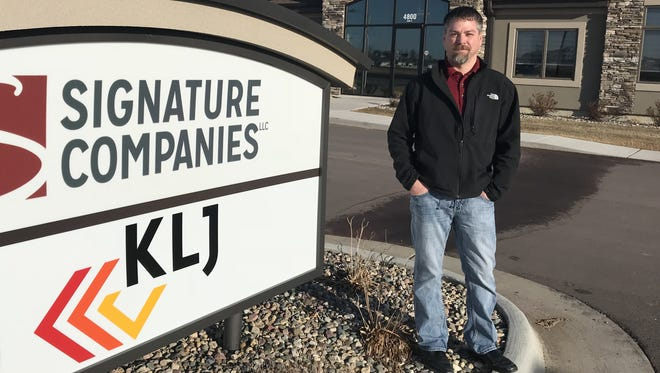 Jeremy Beaty, sales manager for Signature Companies, stands for a portrait outside of the developer's southeastern Sioux Falls office