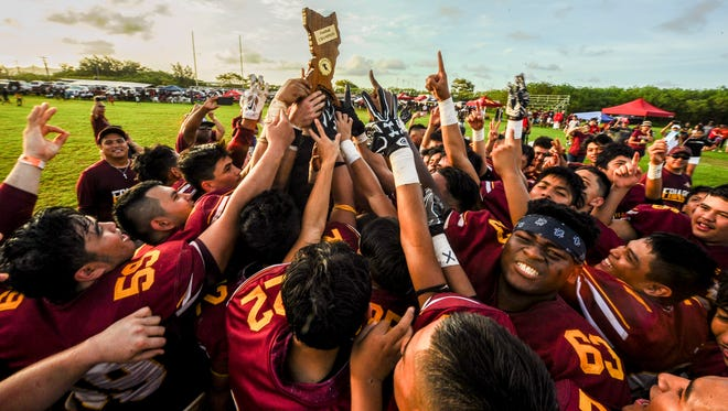The Father Duenas Friars celebrate their 34-0 victory over the George Washington Geckos Saturday the UOG football field. The title win gives FD their third in a row and a chance for next year's team to extend their record 30-game win streak.