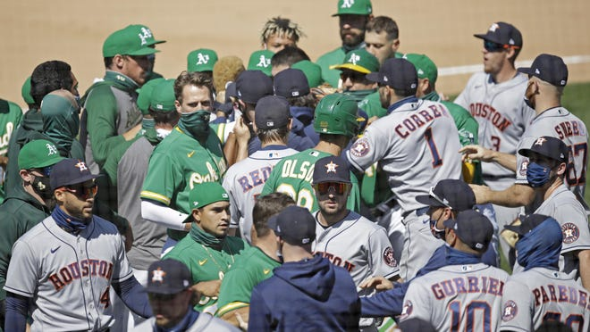 Oakland Athletics and Houston Astros benches clear after Athletics' Ramon Laureano charged the dugout after being hit by a pitch thrown by Astro's Humberto Castellanos in the seventh inning on Sunday.
