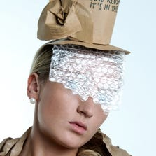 Woman wearing recycled paper hat with bubble wrap veil covering her face