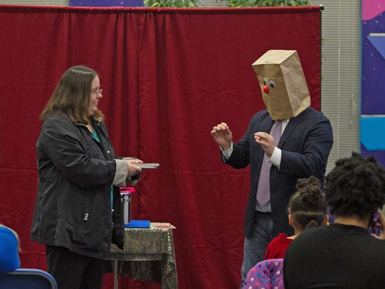 Jimbo Hooten, president of the Middle Tennessee Magic Club inside of the happy face bag, delights his helper and  the audience at Linebaugh Library during an Amazing Abner Youth Magic Group party.