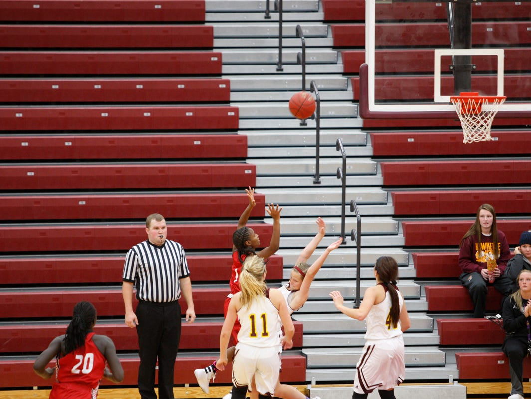 East's Eriana Brown banks in the game-winning basket over Ankeny defender Molly Close at the buzzer to give the Scarlets a 49-48 victory on Friday at Ankeny.