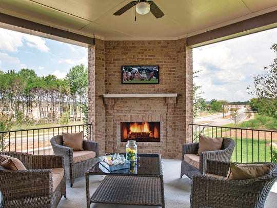 An outdoor living area with a fireplace and TV is a