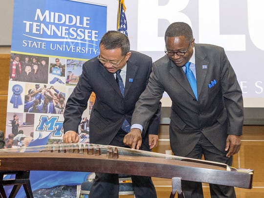 MTSU President Sidney A. McPhee, right, and Hangzhou Normal University President Du Wei pluck a few strings on a guzheng, a Chinese musical instrument, that was donated by Hangzhou Normal as the first instrument for MTSU's new Chinese Music and Cultural Center. MTSU and Chinese dignitaries announced the new center at the MTSU Student Union in March.