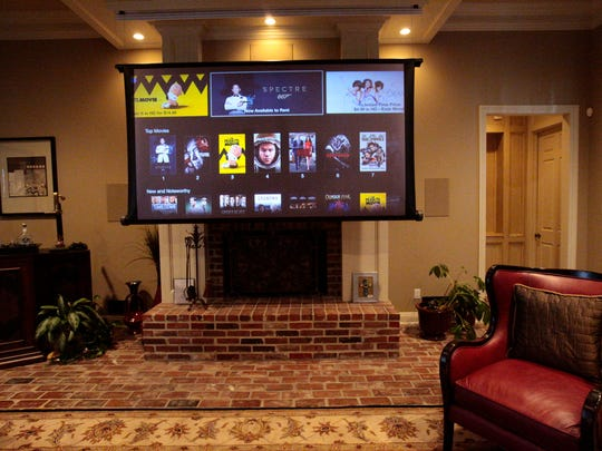 This theater system by Electronics Professionals of Lafayette is concealed in the living room ceiling and drops down with the touch of a button.