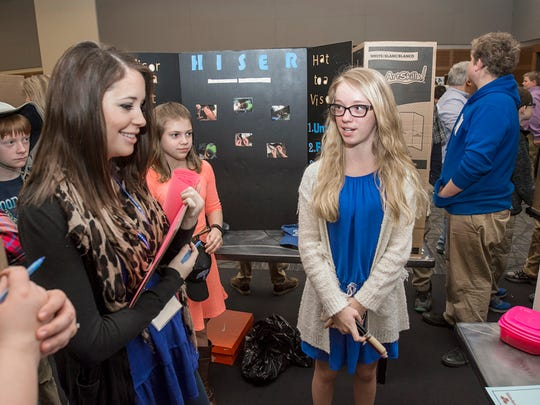 "MTSU graduate student Rachel Matthews, left, who served as a judge for the 24th annual Invention Convention Feb. 25, listens to T.W. Hunter Middle School sixth-grader Elana Ayers of Hendersonville, Tennessee, explain her invention, the ""I PB&J."" Ayers's invention brought home a third-place trophy in her grade's ""Makes Life Easier"" competition. (MTSU photo by Andy Heidt)"