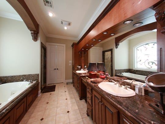 The luxurious master suite has decroative woodwork and huge spa tub.