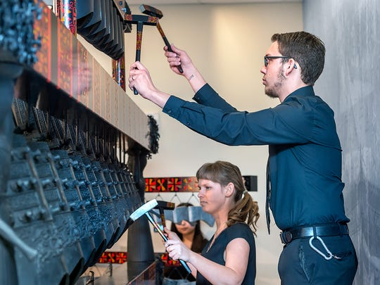 Shelby Shelton and Jeff Upshaw play the bells at the grand opening dedication ceremony for the Center for Chinese Music and Culture in the Miller Education Center.