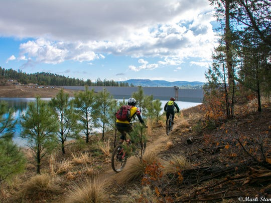 Mountain bikers ride the ridge along Grindstone Lake.