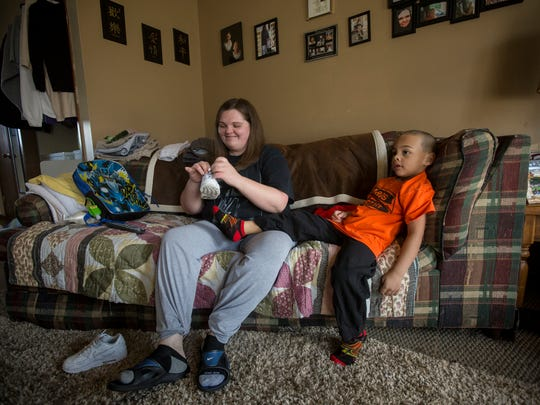March 3, 2016: Jada Walker helps her son, Michaellii, 5, put on his shoes before the bus comes to pick him up for school. Walker has been off heroin since 2009, and says that methadone saved her.