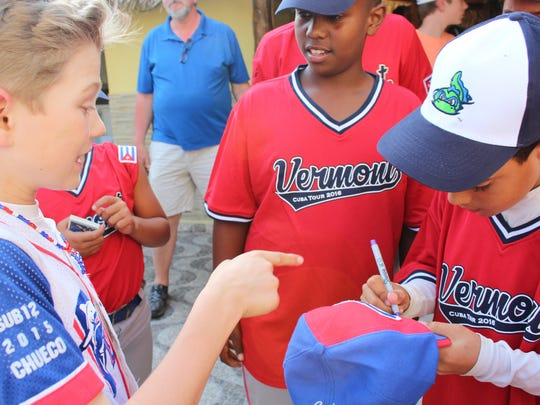 Vermont baseball player Nolan Simon (left) looks on as his hat is signed by a Cuban ballplayer in Havana this past April.
