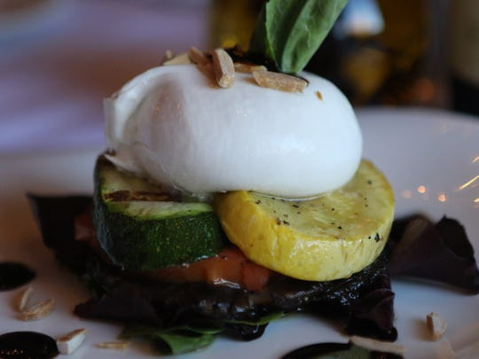 A buratta is shown with grilled squash, micro greens,