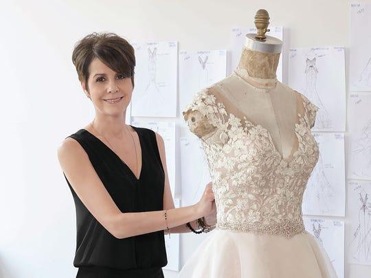 Bridal designer Madeline Gardner poses with a bridal gown.
