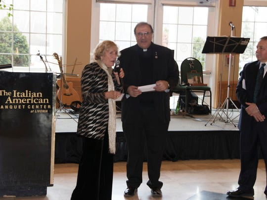 Maria Harris of the IACL Charitable Foundation presents two checks to the Rev. Enzo Addari.