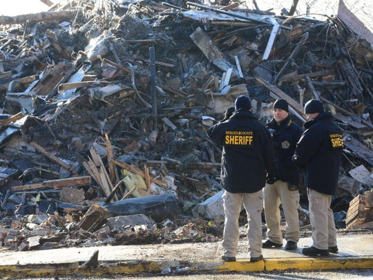 Investigators from the Bergen County Sheriff's Office at the scene of the Edgewater fire in 2015. Smoke was still rising from the AvalonBay complex three days after the blaze began.
