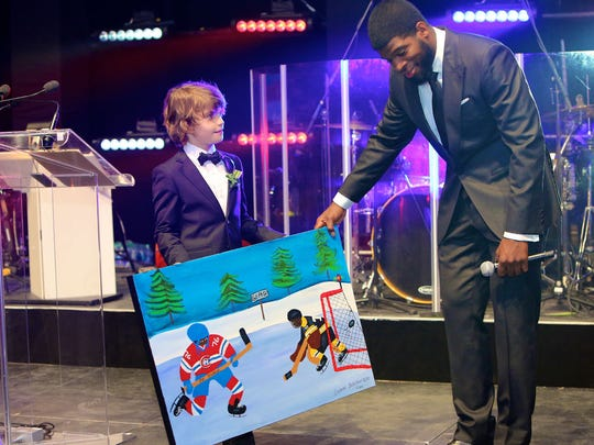 Gabriel, 11, a patient of the Montreal Children's Hospital shows Montreal Canadiens defenseman PK Subban his original artwork in 2015.